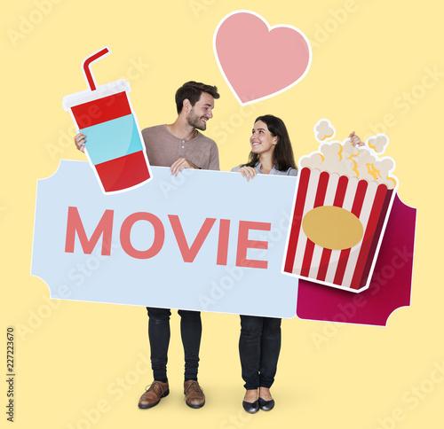 Leinwandbild Motiv Happy couple holding movie icons