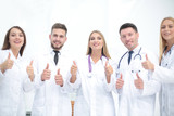 Portrait of a doctor and medical team showing thumb up