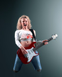 beautiful young blonde woman with a guitar sings a rock song