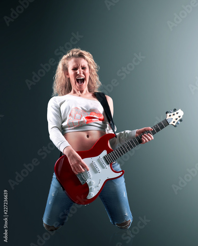 beautiful young blonde woman with a guitar sings a rock song - 227236639