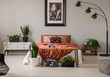 Quadro Plants and lamp in grey bedroom interior with poster on the wall above red bed. Real photo
