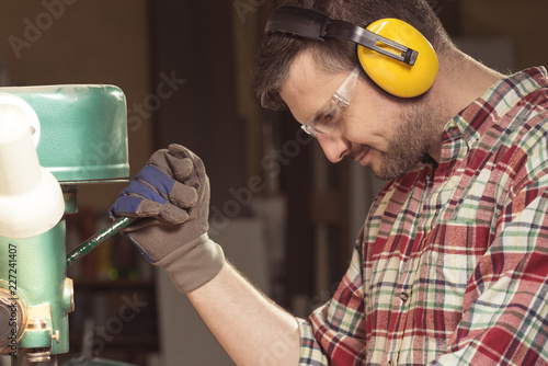 Worker with protective headphones working with a manual wood press - 227241407
