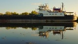 4K. process of boat barges for the carriage of goods in the lock of the Volga-Don ship canal. Ships, water, yellow autumn leaves, beautiful reflection - 227251223
