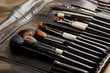 Leinwanddruck Bild - close-up shot of leather holder with professional makeup brushes