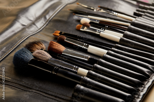 Leinwanddruck Bild close-up shot of leather holder with professional makeup brushes