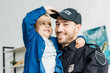 close-up portrait of smiling young father in police uniform carrying his little son and looking at camera