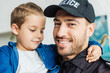 close-up portrait of happy young father in police uniform carrying his little son and looking at camera
