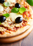 Pizza with mozzarella, mushrooms, black olives and fresh basil. Italian pizza. Homemade food. Symbolic image. Concept for a tasty and hearty meal. Rustic wooden background. Selective focus. Close up.  - 227270491