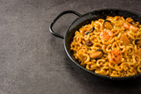 Traditional Spanish fideua. Noodle paella on black stone. Copyspace - 227270624