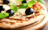 Pizza with mozzarella, mushrooms, black olives and fresh basil. Italian pizza. Homemade food. Symbolic image. Concept for a tasty and hearty meal. Rustic wooden background. Selective focus. Close up.  - 227272803