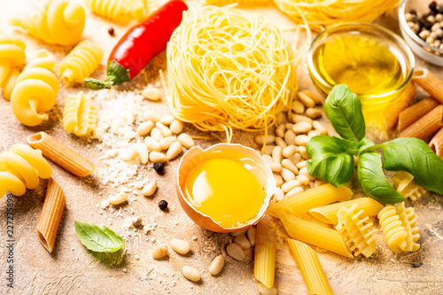 Foto Murales Healthy raw ingredients for italian pasta sauce Carbonara with egg, grated cheese, pine nuts, basil and assorted pasta. Food background.