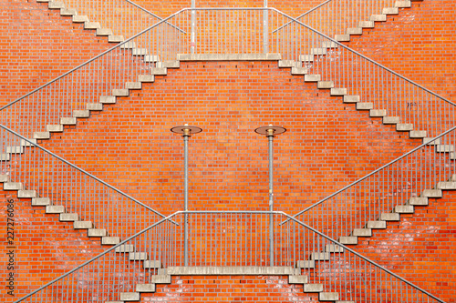 some symetrically stairways in front of a red brick wall