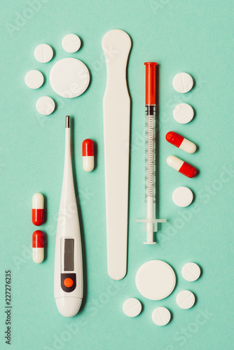 Foto Murales top view of medicines, electronic thermometer and syringe on green