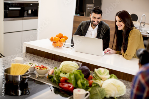 Foto Murales Couple looking at laptop in modern kitchen