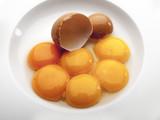 Varios huevos rotos dentro de un plato redondo blanco  2 - 227284406