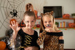Portrait of beautiful Caucasian girls with painted faces fooling in smart Halloween dresses and smiling at camera joyfully