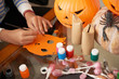 Close-up view of unrecognizable child sitting at table with pumpkins and painting diy paper mask while getting ready for Halloween