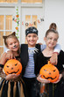 Quadro Portrait of Caucasian kids in cool Halloween costumes with painted faces holding pumpkins and smiling at camera cheerfully