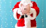 Santa holding a piggy bank on a shiny light blue background - 227289044