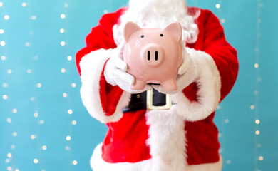 Santa holding a piggy bank on a shiny light blue background