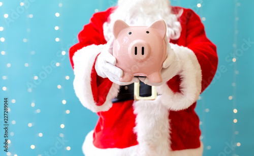 Santa holding a piggy bank on a shiny light blue background - 227289044