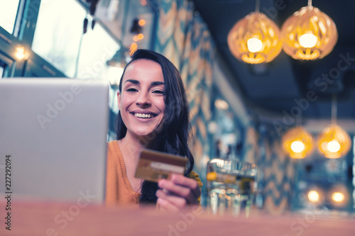 Leinwandbild Motiv Work with pleasure. Beautiful brunette expressing positivity while going to do online shopping