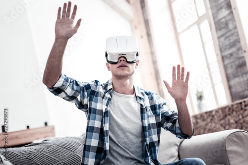 Foto Murales Virtual reality. Calm young man sitting on the sofa and putting his hands up while wearing virtual reality glasses