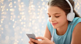 children, technology and people concept - close up of happy girl with smartphone and headphones listening to music over festive lights background