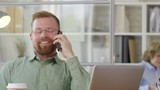 Joyous Caucasian office worker sitting at desk, smiling and chatting on mobile phone - 227295417