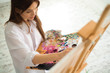 Artist close-up painting flowers. - 227300033