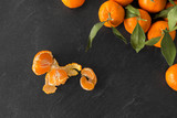 food, healthy eating and vegetarian concept - close up of mandarins with leaves on slate table top