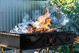 Metal grill, forged, handmade, with a pattern. A hot fire on the wood with smoke for barbecue and grilled products. Outside on a Sunny day.