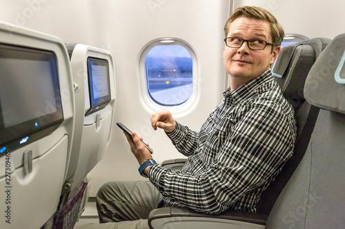 Mann schaut, im Flugzeug sitzend, in Richtung der Stewardess