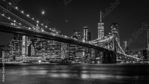 Brooklyn Bridge in New York mit Manhattan Skyline bei Nacht in schwarz/weiß