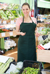 Female grocery worker welcoming to vegetable store