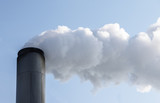 chimney with thick clouds of smoke or steam, concept for economic growth and environmental pollution by co2 and fine dust, blue sky, copy space - 227337610