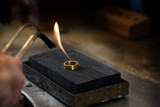 golden ring is annealed with a gas flame in a jewelry factory, copy space in the dark background, selected focus, narrow depth of field - 227343699