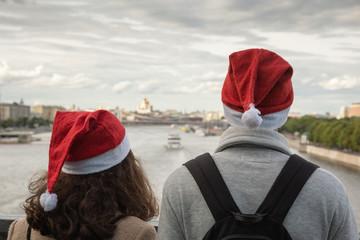 Girl and guy on the bridge in Santa's hat