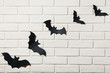 Halloween paper bats on white brick wall background