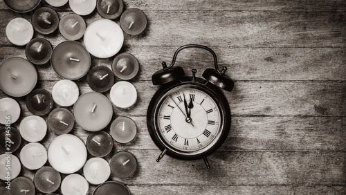 Retro alarm clock with candles on wooden background. Image in black and white color style © Masson