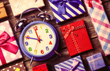 colorful gifts and blue clock on the brown wooden table - 227346031