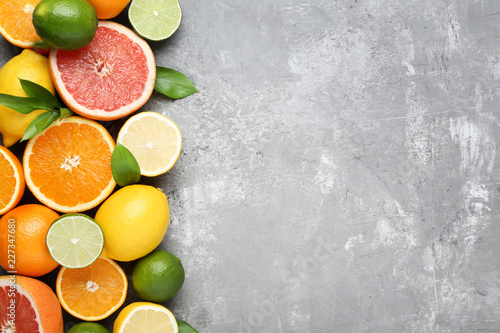 Leinwanddruck Bild Citrus fruits with green leafs on grey wooden table