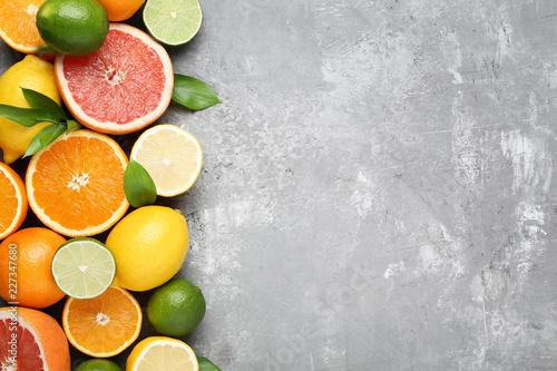 Leinwandbild Motiv Citrus fruits with green leafs on grey wooden table