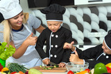 A family of cooks.Healthy eating. Happy family mother and children prepares vegetable salad in kitchen	 - 227348690
