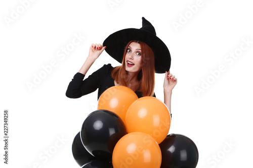 Leinwandbild Motiv Beautiful redhaired woman in halloween costume with balloons on white background