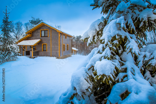 Winter cottage. Country house. Two-storeyed mansion. Country house building. Camping.   Wooden house. Christmas tree covered with snow. © Grispb