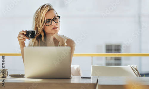 Poster Businesswoman having coffee and thinking at cafe