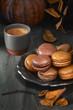 Leinwandbild Motiv Autumn macarons with caramel and cocoa with coffee on dark rustic wood