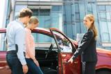 Dealer Opening Car Door For Young Couple - 227401823