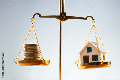 Stacked Coins And House Model Balancing On Justice Scale